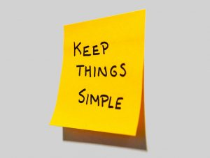keep things simple written in black on a yellow stick on note on a wall